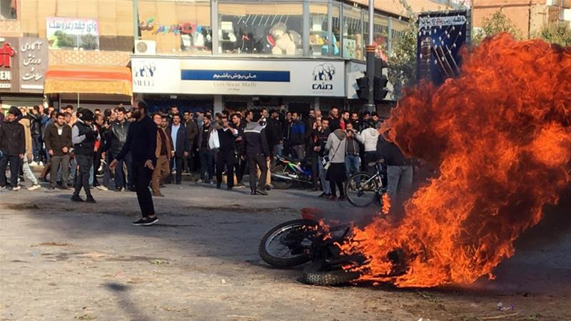 Protesters clashed with police and security forces in cities and towns across Iran after the price rise announcement [EPA]