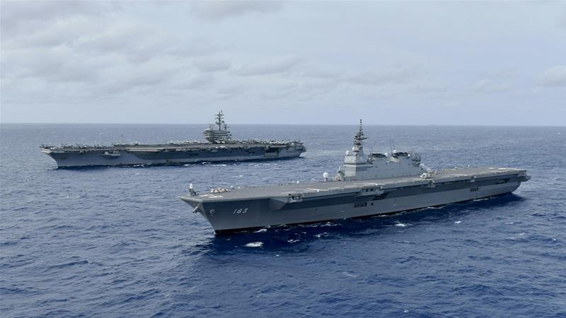 The aircraft carrier USS Ronald Reagan and Japan Maritime Self-Defence Force helicopter carrier JS Izumo in operations in the disputed South China Sea [File: JMSDF/US Navy/Handout via Reuters]