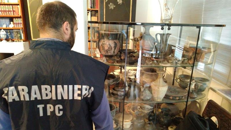 A photo provided by Carabinieri military police shows an officer inspecting artefacts in a display case in Cosenza, Italy [Reuters]