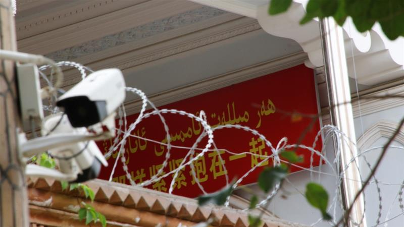 A propaganda banner and a security camera are placed on the walls of a mosque in the Old City in Kashgar, Xinjiang Uighur Autonomous Region, China. [Thomas Peter/Reuters]