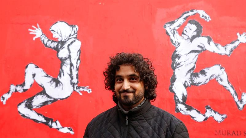 Yemen's street artist Murad Subay poses after unveiling a street painting to denounce the bloody conflict [Christian Hartmann/Reuters]