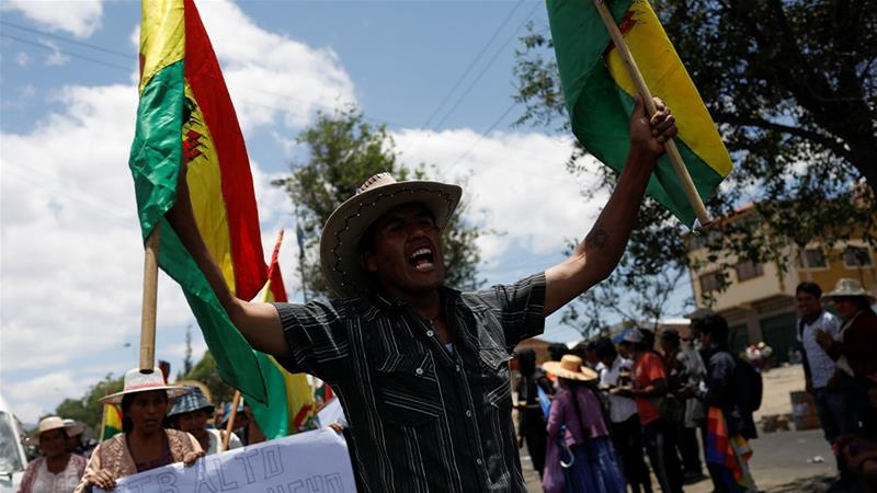 Man waving Bolivian flags alongside fellow coca farmers and supporters of Bolivia's former President Evo Morales during a blockade of an entrance to Sacaba, near Cochabamba, Bolivia [Marco Bello/Reuters]