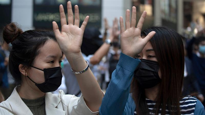 Protesters hold up their hands to represent their five demands including universal suffrage [Ng Han Guan/AP Photo]