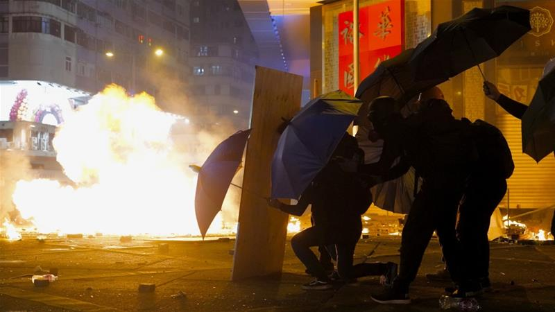 Protesters protect themselves from tear gas canister using umbrellas in the Kowloon area of Hong Kong. As night fell in Hong Kong, police tightened a siege on Monday at a university campus as hundreds of anti-government protesters trapped inside sought to escape [Vincent Yu/The Associated Press]