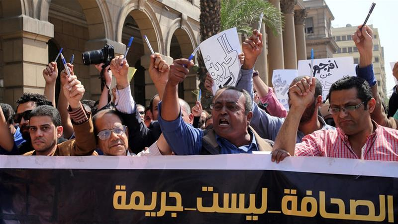 Egyptian journalists hold up pens and a banner reading 'journalism is not a crime' during a protest in Cairo [File: Khaled Elfiqi/EPA]