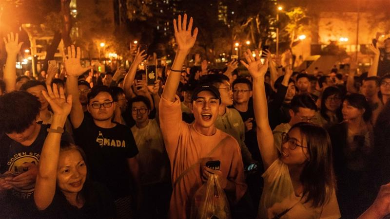 Hong Kong residents celebrated outside polling stations on Sunday after pro-democracy candidates won district council elections by a landslide [Billy HC Kwok/Getty Images]