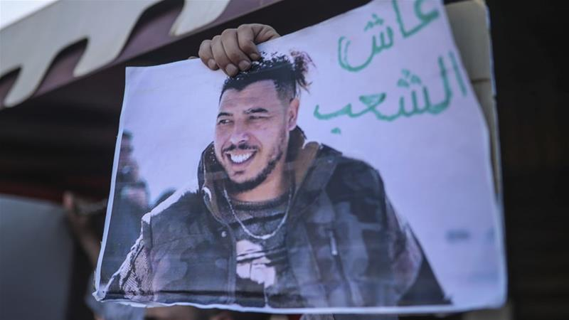 Protesters place a photo of Moroccan rapper Gnawi outside a court where he was on trial [Mosa'ab Elshamy/AP]