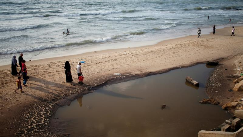Palestinians walk past a pool of sewage on a beach in the northern Gaza Strip July 13, 2018. Picture taken July 13, 2018 [Mohammed Salem/Reuters]