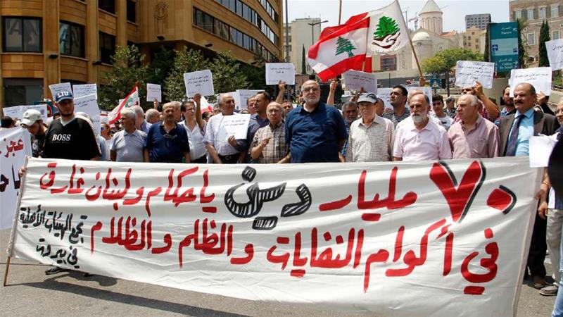 These Lebanese protesters' banner reads: 'Oh rulers of Lebanon, our debt is 70 billion and the county is drowning under piles of trash, injustice and darkness' [Nabil Mounzer/EPA]