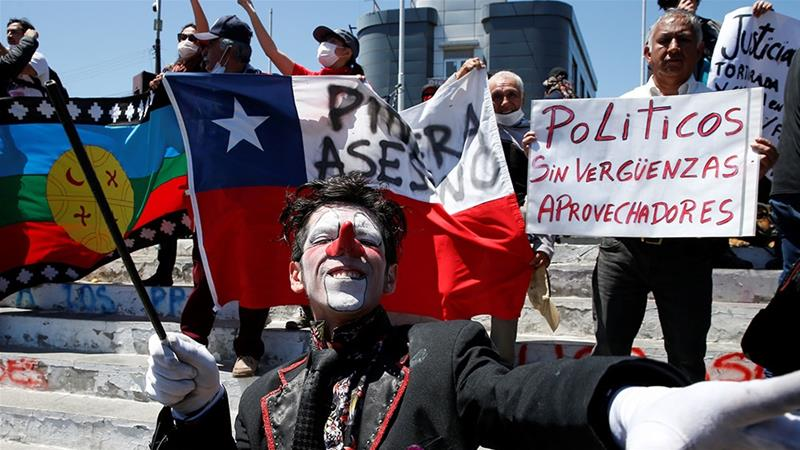 A person dressed as a clown takes part in a protest against Chile's state economic model in Valparaiso, Chile as a man behind him holds a  placard that reads 'Shameless and freeloading politicians' [Rodrigo Garrido/Reuters]