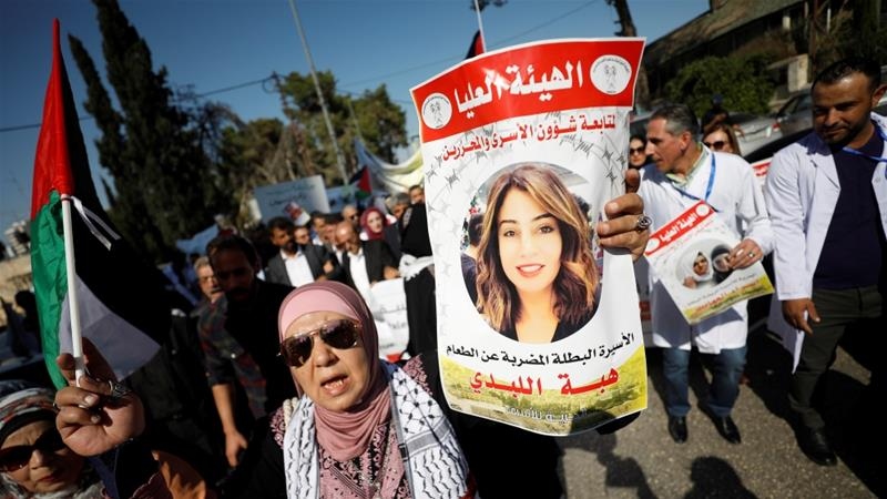 A demonstrator holds a picture of Jordanian citizen Hiba Labadi during a protest calling for the release of Labadi and Palestinian prisoners from Israeli jails, in Ramallah in the Israeli-occupied West Bank [Mohamad Torokman/ Reuters]