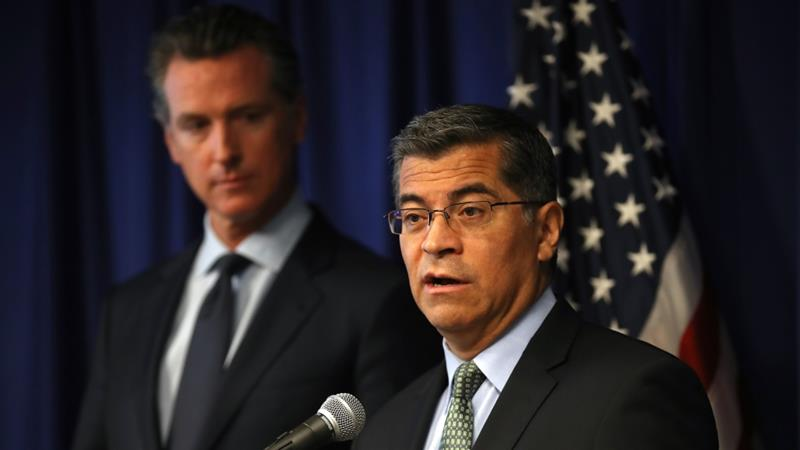 California attorney general Xavier Becerra, right, speaks as California Governor Gavin Newsom looks on during a news conference in Sacramento [File: Justin Sullivan/Getty Images/AFP]
