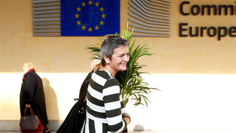European Competition Commissioner Margrethe Vestager holds a plant received by climate activists during a protest in front of European Commission headquarters in Brussels [Francois Lenoir/Reuters]