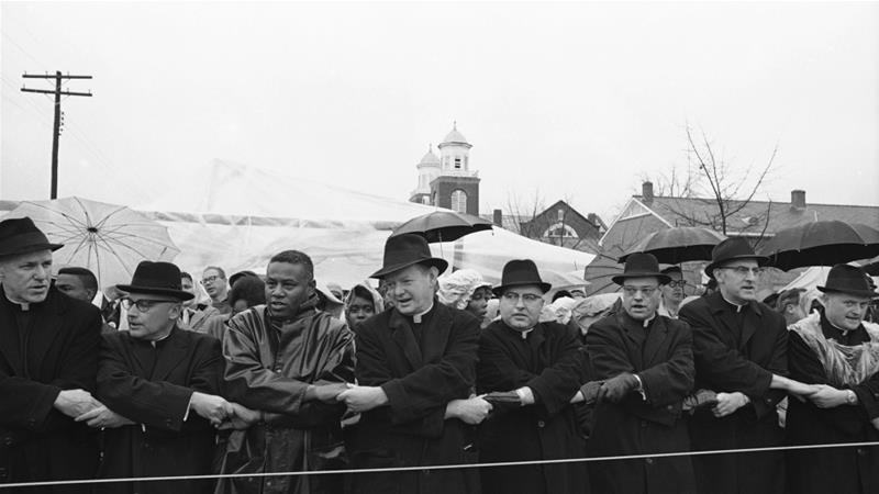 Several clergymen stand at a rope barricade known as the 'Berlin Wall' and sing freedom songs with demonstrators at Selma, Alabama, March 13, 1965 [File: AP Photo]