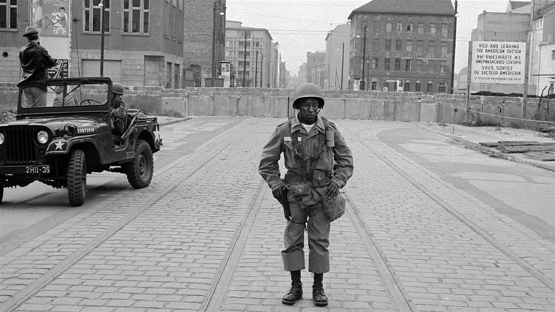 West Berlin, 1961: An American soldier stands guard in front of the Berlin Wall [Leonard Freed/Magnum Photos]