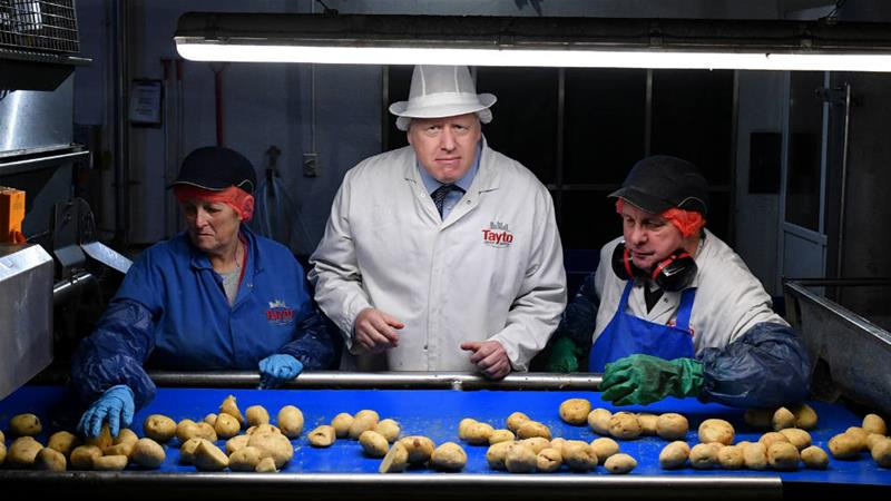 Johnson visited the Tayto Castle potato crisp factory on a campaign stop in Northern Ireland [Daniel Leal-Olivas/Pool/Reuters]