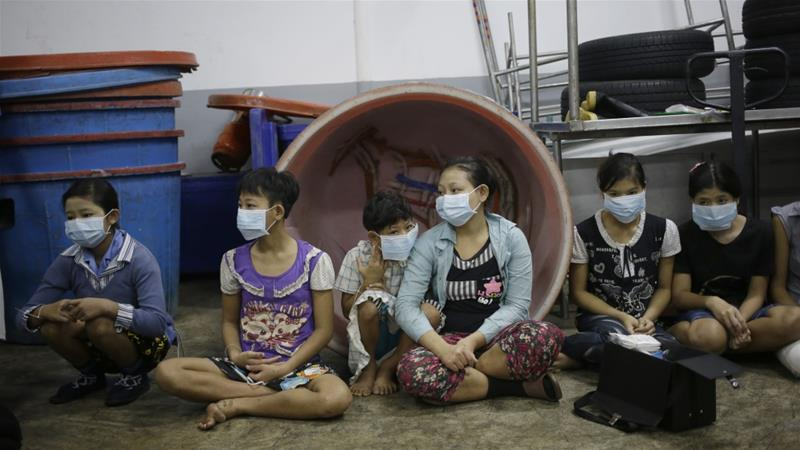 Children and teenagers sit together to be registered by officials during a raid on a shrimp shed suspected of using slave labour in Samut Sakhon, Thailand on November 9, 2015 [File: Dita Alangkara/AP]