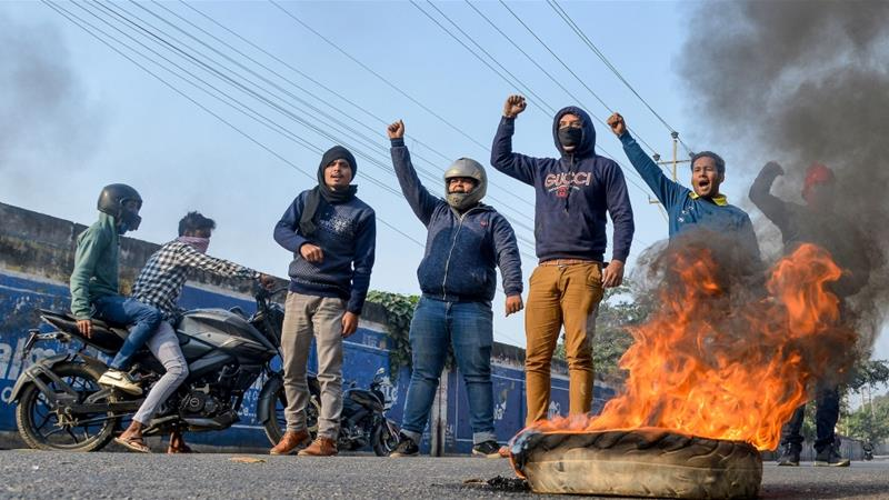 Protesters shout slogans as they burn tyres during a strike called by students organisation, NESO, against the federal government's Citizenship Amendment Bill [Biju BORO/AFP]