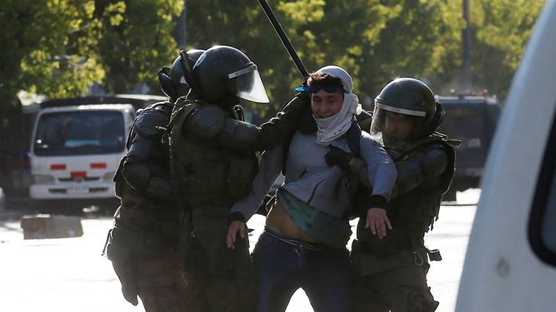 Security forces detain a demonstrator during a protest against Chile's government in Valparaiso, Chile [Rodrigo Garrido/Reuters]