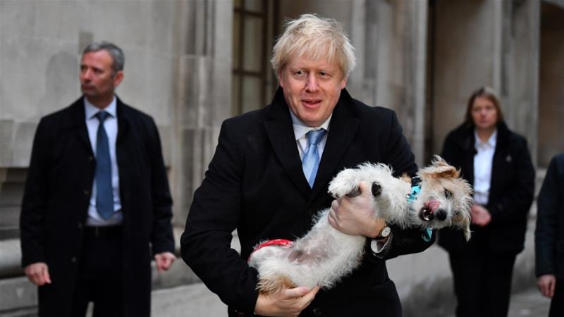 The UK's Prime Minister Boris Johnson holds his dog Dilyn as he leaves a polling station after voting in the general election in London [File: Dylan Martinez/Reuters]