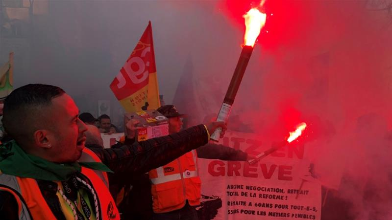 French railway workers light flares during a Paris protest in France's 13th day of consecutive strikes against pension reform plans [Jean-Michel Belot/Reuters]