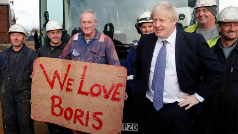 Boris Johnson posed with workers during election campaigning, having pledged to maintain EU standards of workers' rights [Frank Augstein/Pool/Reuters]