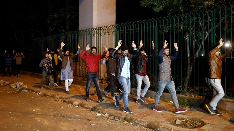 Police made students raise their hands as they forced them to leave the Jamia Millia Islamia campus [Adnan Abidi/Reuters]