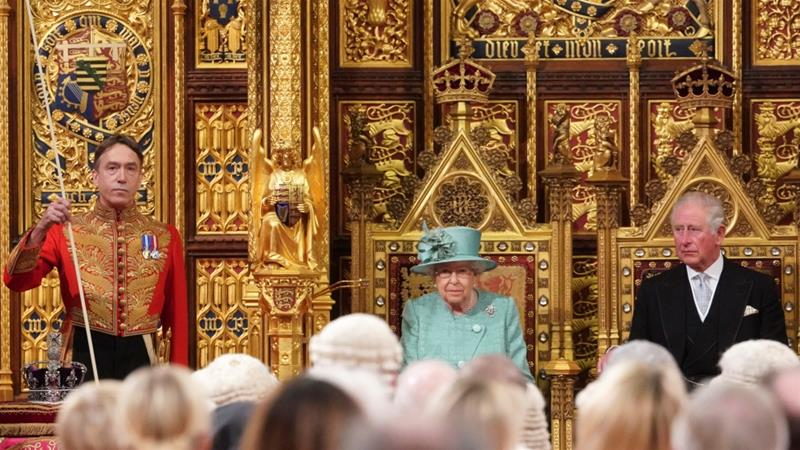 Britain's Queen Elizabeth takes her seat on the Sovereign's Throne next to Prince Charles before reading the Queen's Speech during the state opening of Parliament in London [Hannah McKay/Pool/Reuters]