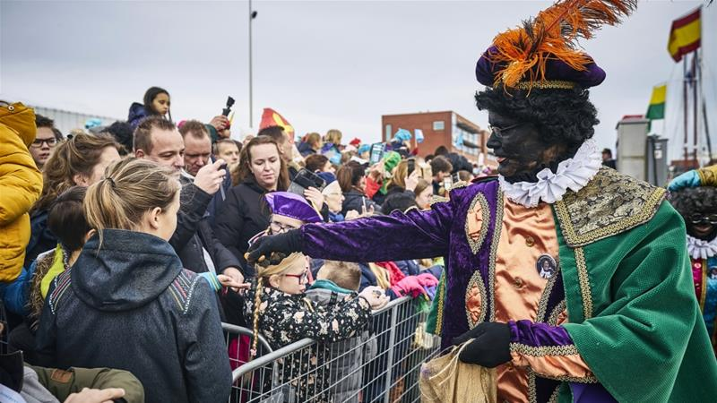 Black Pete hands out treats during the arrival of Dutch Saint Nicholas, or Sinterklaas, in Scheveningen [Phil Nijhuis/ANP/AFP]