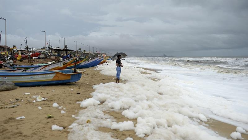 A man looks on as foamy discharge, caused by pollutants, mix with surf at Marina Beach in Chennai [Arun Sankar/AFP]
