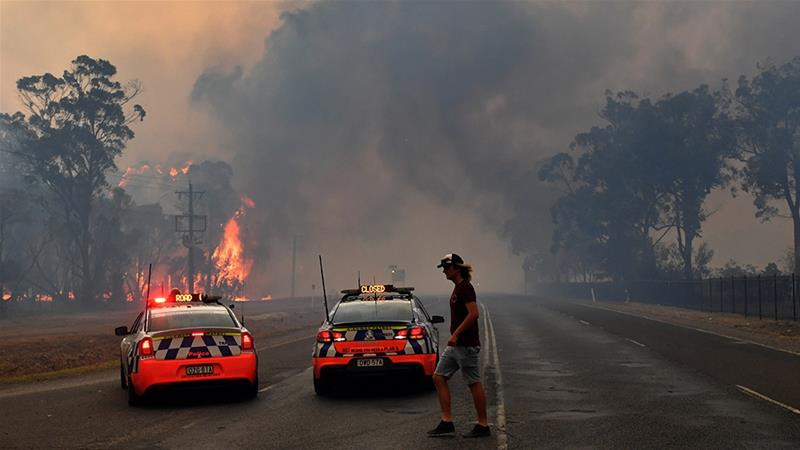 Australia's prime minister, who was criticised for taking a holiday in Hawaii as the fires raged, cut short his trip and offered an apology after the deaths of two firefighters [Dean Lewins/AAP Images via Reuters]
