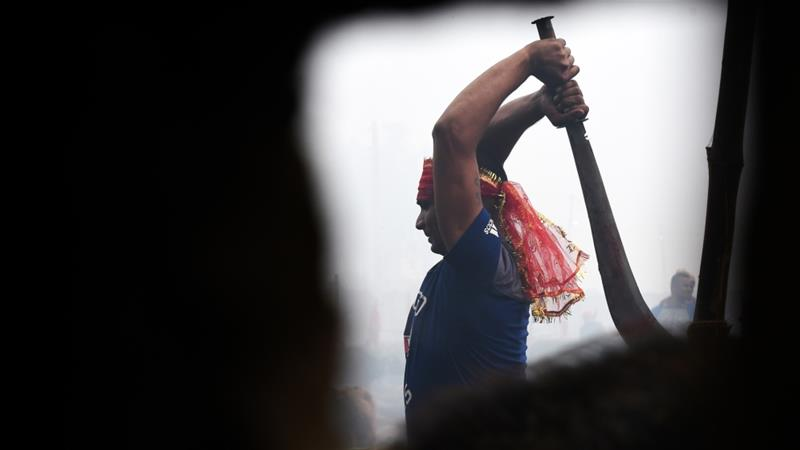 A Hindu devotee slaughters a buffalo as a offering during the Gadhimai Festival in Bariyarpur on Tuesday [Prakash Mathema/AFP]