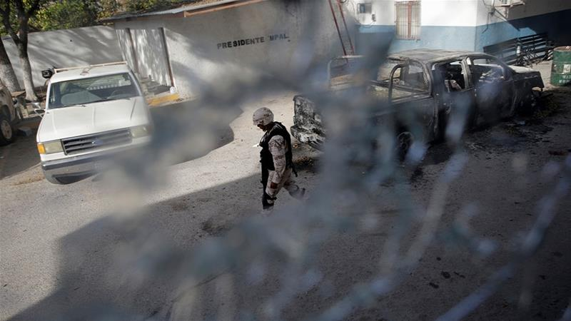 A military police officer standing near the bullet-riddled town hall building of Villa Union days after a gun battle between police and hitmen in the state of Coahuila, Mexico [File: Daniel Becerril/Reuters]