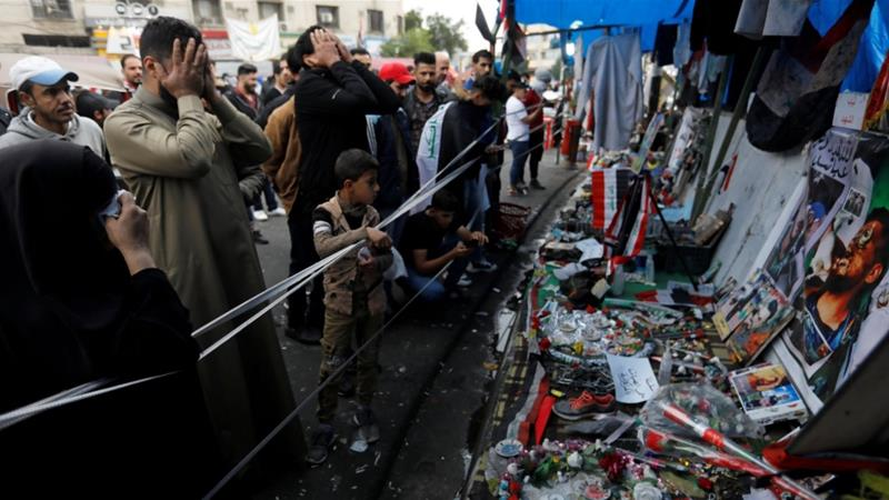 Iraqi demonstrators react as they look at a makeshift memorial with the personal belongings of those who were killed during anti-government protests at Tahrir Square in Baghdad [File:Khalid al-Mousily/Reuters]