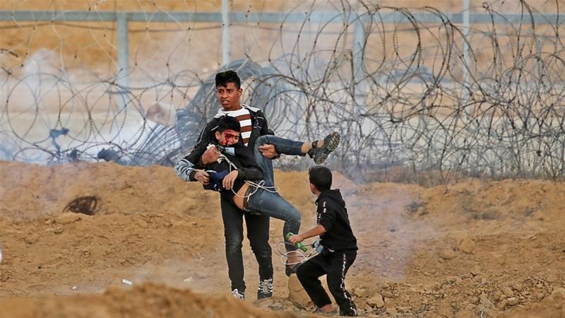 A boy tries to evacuate a wounded Palestinian child during a protest at the Israel-Gaza perimeter fence in the southern Gaza Strip [Ibraheem Abu Mustafa/Reuters]