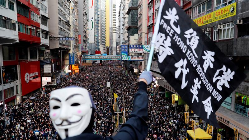 A protester wearing a Guy Fawkes mask waves a flag during the mass march on Sunday [Danish Siddiqui/Reuters]