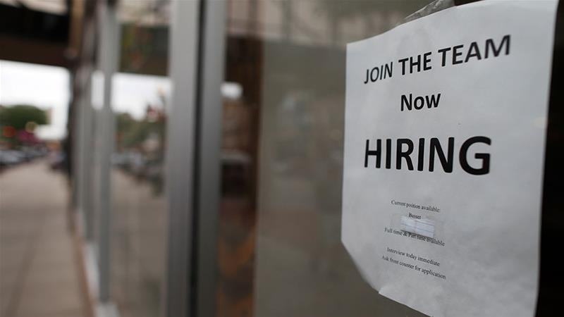 A ''now hiring'' sign hangs in the window of business in downtown Fargo, North Dakota [File: David Zalubowski/AP Photo]