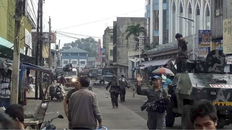 Soldiers and police cordon off the area after two bombs exploded outside a Roman Catholic cathedral in Jolo, the capital of Sulu province. [WESMINCOM Armed Forces of the Philippines via AP Photo]