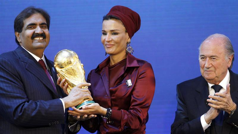 Qatar's then emir and his wife hold a copy of the World Cup received in 2010 after it was awarded [Arnd Wiegmann/Reuters]