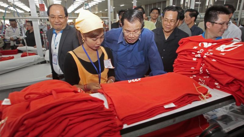 Prime Minister Hun Sen (centre) visiting a garment factory outside of Phnom Penh in 2017 [File: Heng Sinith/The Associated Press]