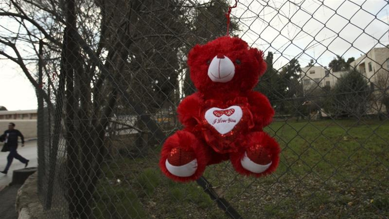 A 'Valentine's Day' teddy bear hangs on a fence in the West Bank city of Ramallah on February 13, 2011 [File: Mohamad Torokman/Reuters]