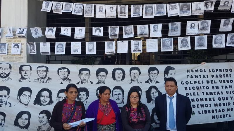 After filing a motion, Maya Achi women and their lawyers stand outside the Constitutional Court, adorned with pictures of Guatemalans killed and disappeared during the 36-year armed conflict [Lisa Rankin/Al Jazeera]