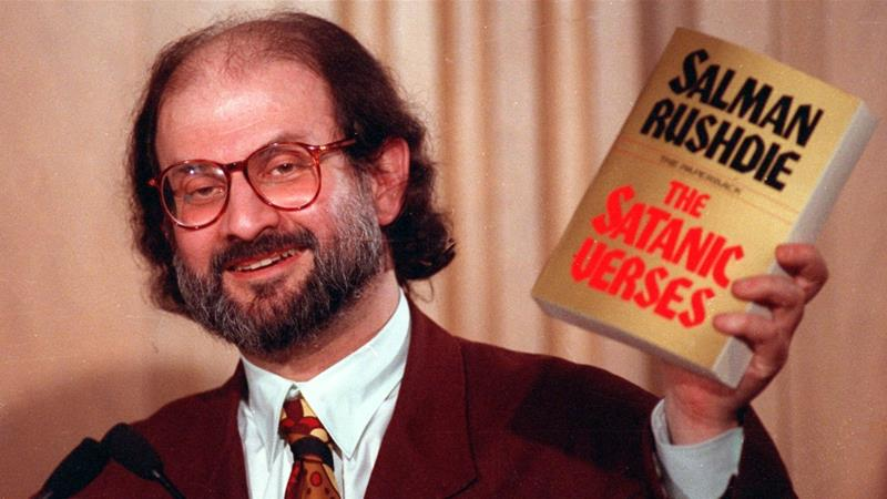 Salman Rushdie holds up a copy of his book 'The Satanic Verses' at the Freedom Forum in Arlington, Virginia in March 1992 [File: AP Photo/Ron Edmonds]
