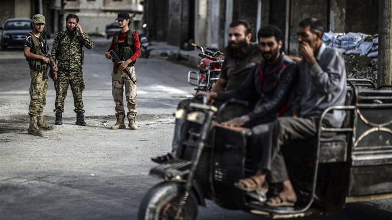 Fighters from the Syrian opposition stand near a checkpoint in Idlib city last October [Ugur Can/DHA via AP]