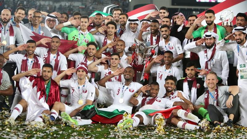 Qatar players and coaching staff pose with the trophy after winning the Asian Cup [Suhaib Salem/Reuters]