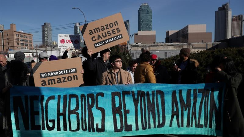 Demonstrators hold signs during a protest against Amazon in the Long Island City section of the Queens borough of New York, US, February 14, 2019 [Shannon Stapleton/Reuters]