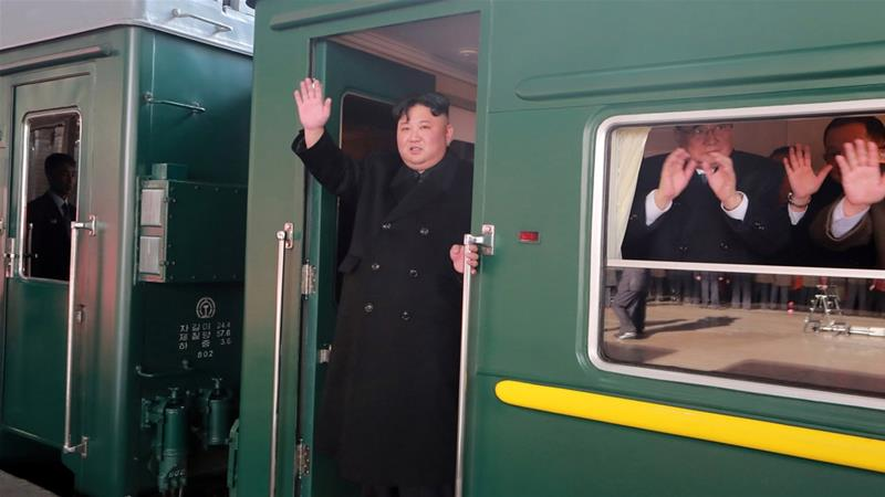 North Korean leader Kim Jong Un waves from a train as he departs for a summit in Hanoi [KCNA via Reuters]
