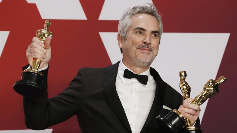 Alfonso Cuaron of Mexico poses with his Best Director, Best Foreign Language Film and Best Cinematography awards for Roma [Mike Segar/Reuters]