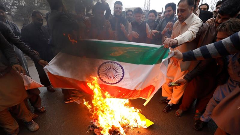People burn a poster depicting India's flag against what they call airspace violation by Indian jets in a protest in Peshawar [Fayaz Aziz/Reuters]
