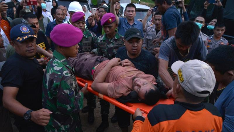 Rescuers carry a miner who survived following the collapse of an illegal gold mine at Bolaang Mongondow region [Antara Foto/Adwit B Pramono/via Reuters]